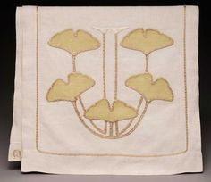 Around appliquéd ginkgo leaves, the border is done with a couching stitch, where a thread is sewn down at right angles at short intervals (antique, Stickley).