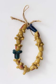 This is a string of fifteen beads in the form of floral pendants pierced lengthwise. Fifteen are mustard-yellow; one bead is blue green and another is dark blue. They are in perfect condition.