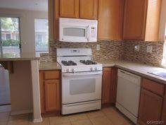 Tile backsplash in builder grade kitchen. Light oak cabinets. Kitchen remodel / makeover with simple changes.