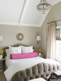 Designer Kelie Grosso envisioned the master bedroom as a soft, platinum respite, but she couldn't resist punching it up with a vibrant dose of color, a hot pink bolster pillow. A Morgan bed by Cisco Brothers is upholstered in Schumacher's Gainsborough Velvet. Walls are painted Edgecomb Gray by Benjamin Moore.   - HouseBeautiful.com
