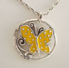 "This fab necklace has a colorful yellow butterfly on one side and a simpler embossed design on the other side. The pendant has a 1-5/8"" diameter, and the chain is 16"" with an additional 2"" extension."