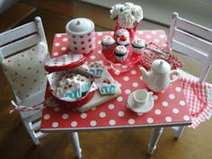miniature table with red/white polka dots, little white chairs, tin of cookies-it's just marvelous