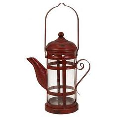 Metal candle lantern with teapot silhouette.  Product: LanternConstruction Material: Tin and glassColor: RedAccommodates: (1) Candle - not includedDimensions: 10.5 H x 8.5 W x 5.25 D