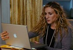 The ever-so-chic Carrie Bradshaw and her ode to the Mac. Outfit: pearl necklace + gray cardi + LBD. / J'adore her wavy hair!