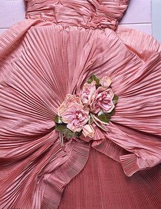 Keenly historicist, Balenciaga invented a fantasy of eighteenth-century court dress, knowing that Marie-Antoinette favored overdresses with swags anchored by roses. Sustained by wide panniers also appropriated from eighteenth-century fashion, Balenciaga renewed the Rococo rose for the 1940s and 1950s.