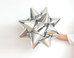 London Based Designer Stephen Johnson's shiny aluminum Happy Happy Gift Bow wall lamps.  I'd love one for the salon at Christmas