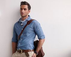 Blue shirt with folded sleeves and beige chinos look good with brown accessories