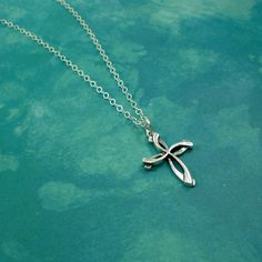 This large swirl cross necklace is made with sterling silver components. Perfect for everyday wear. - 18-22 inch sterling silver cable chain with spring clasp - Large Swirl Cross pendant: 30 x 21 mm -