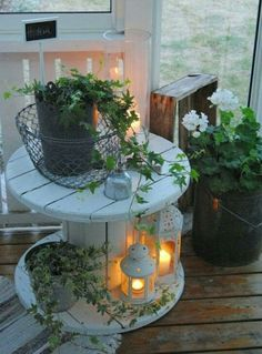 White industrial spool side table with plants & lanterns