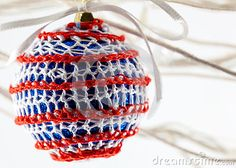 A close up  of a glittery bauble covered in red and white crotchet