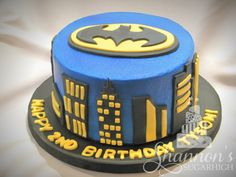 Round blue buttercream Batman cake with airbrushing, and a fondant skyline and Batman symbol. Chocolate cake with chocolate buttercream filling. Keywords: birthday, boy, Superhero.