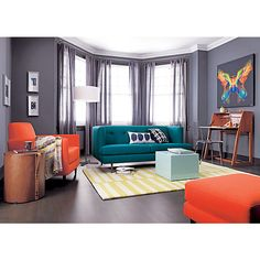 I love all these pops of color against the gray walls and I LOVE the peacock blue sofa!!! If it wasn't $1,200 it would be mine.