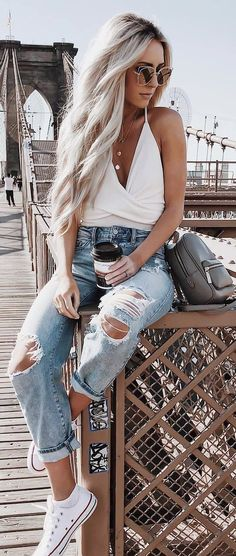 Summer or spring outfit. White, low cut, wrap tank top paired with light washed ripped jeans. Love her bleach blonde hair, sunglasses, and layered necklaces. Her small book bag is super cute too.