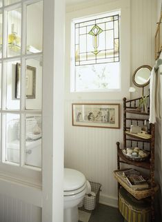 Toilet sectioned off by glass top door. I like this whole look but I think the corner shelf would get in the way