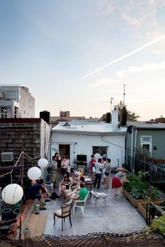 Rooftop party with vegetable garden, dog, and IKEA pendant lights.
