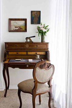 um espaço especial na sala para a escrivaninha e a cadeira antiga pertencentes