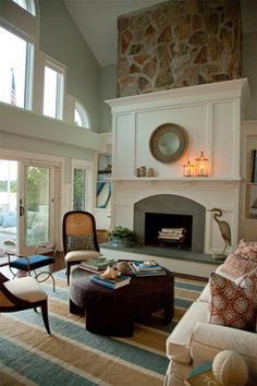 Family Room - Living Room - Cathedral Ceiling - Striped Rug - Cream Sofa - Caneback Chairs - Natural Fiber Woven Round Coffee Table - Seashell Decor - Slate Fireplace - Raised Hearth - Round Mirror - Lantern Decor - Crane Statue - Egret Statue - Stone Fireplace - Custom Millwork