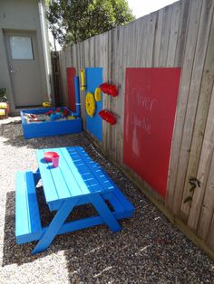 Small outdoor play area beside house: sandbox, picnic table, wall activities