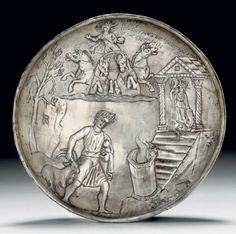 Roman silver bowl, 3rd century A.D. A sacrifice scene in relief, with a youthful priest  gripping a goat by its horn, leading it toward a flaming hexagonal altar situated at the base of the steps of a temple to Minerva, with nimbate Helios driving his quadriga above, Greek inscription to reading Nonnos, priest, worshipper of Pallas, made an offering, 16.5 cm diameter. Private collection