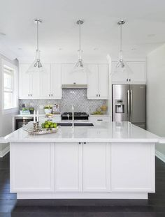 Beautiful gray and white kitchen boasts a white kitchen island accented with a white marble countertop fitted with a stainless steel sink paired with a polished nickel gooseneck faucet lit by three glass cone shaped light pendants.