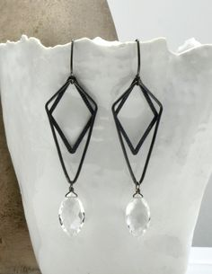 Oxidized sterling silver diamond shapes with quartz crystal drops earrings. Hangs from almond shaped handmade earwires. Calliope Jewelry.