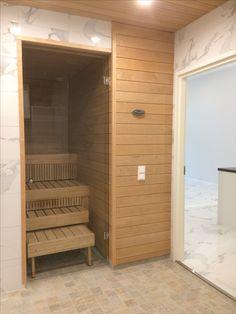 Kakkosasunnon kylpyhuoneen valkoinen marmorikuvioinen laatta jatkuu saunaan ja paneeli taas jatkuu kylpyhuoneen seinällä. Divider, Garage Doors, Outdoor Decor, Room, Furniture, Home Decor, Bedroom, Decoration Home, Room Decor