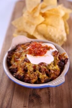 Full of ground beef, beans, and Cheddar cheese, this hearty dip is a crowd-pleasing appetizer. the chew The Chew Recipes, Dip Recipes, Mexican Food Recipes, Snack Recipes, Cooking Recipes, Potluck Recipes, Party Recipes, Bean Recipes, Sauces