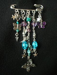 Silver (coloured) Kilt Pin Brooch.  Made with a mix of silver chain, butterflies, stars and wings charms, amethyst and turquoise (coloured) beads.