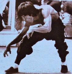 "A rare photo of Bruce Lee doing monkey kung fu on the set of ""Enter the Dragon""."