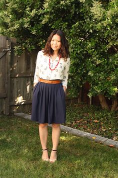 Cream/white (possibly patterned) top, with red dangly beaded necklace, brown belt, flowy silky dark blue knee-length skirt.