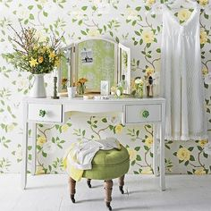 A dressing area in a bedroom is a lovely spot for spring florals and here they feature on a large-scale trailing wallpaper design that has been used from floor to ceiling, on bright drawer pulls and in fresh form in enamelware jugs and glass vases. White painted furniture lets the paper behind shine, while a sweet round stool provides the perfect perch