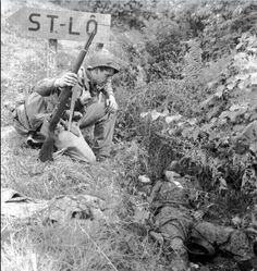 "An American infantryman observes a dead Waffen-SS Grenadier of 17th SS ""Götz Von Berlichingen' in the battle area of St Lo"