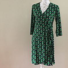 { New York & Co } green and black wrap dress Geometric print in black and green. Faux wrap dress (looks like a wrap dress with a tie at the side, but skirt is attached at the side seam). Polyester and spandex blend, with a bit of stretch and won't wrinkle! Machine wash cold and hang to dry, it will turn out perfect. New York & Company Dresses