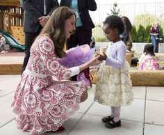 The Duchess of Cambridge receives flowers from a little girl at the Immigration Services Society in Vancouver, B.C., Sunday, Sept 25, 2016.