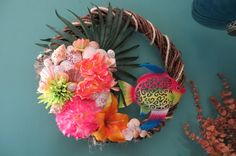 This tropical fish beach wreath in vibrant colors brings a cheerful and lively feel to your home. The metal tropical fish is brightly colored and has a pretty scrolled cutout design adding much interest. The tropical looking florals are brightly colored in pink, coral, yellow and lime green and are set upon a palm leaf. The wreath is wrapped with rope trim for an even more nautical feeling. I have also placed a variety of shells among the florals. The shells include scallops, polished pearl…
