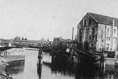 The Warandebrug was blown up during the First World War. The Warandebrug was a railway bridge on the line Bruges, Blankenberge. The stack houses in the background in this picture have been replaced by the firehouse. The chimney that we can see, is from the yeast factory.