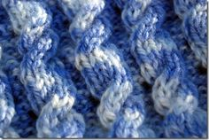 Close up of reversible cable baby blanket pattern for hand or machine knitting
