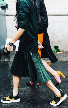 Dress down a pleated midi skirt with a pair of slip-on sneakers.