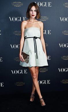 Alexa Chung wears a strapless Valentino mini dress with lace-up heels and a metallic clutch