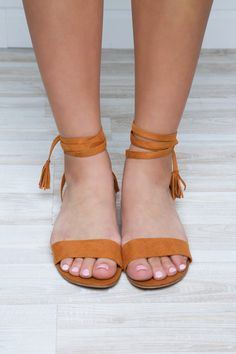 Sweet victory! These Stay in Charge Sandals in tan feature a faux suede material with straps that crisscross up the ankle for a customized fit. Toe strap, slip on design. Ankle strap. Cushioned insole