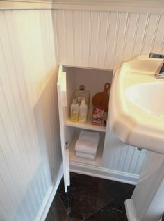 Built-in bathroom wall storage shelves are storing shampoo, conditioner, perfume, bar soap, a handheld mirror, and face towels.