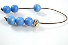 Mini worry bead or begleri with six blue wooden beads (12 mm), silver plated decorative bead and brown cord.   Μπεγλέρι που αποτελείται από έξι μπλε ξύλινες χάντρες (12 mm) και επάργυρα μεταλλικά στοιχεία σε καφέ κορδόνι.