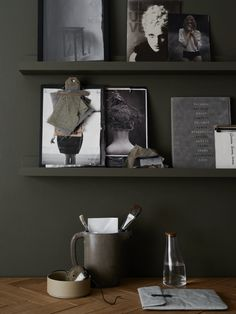 Dark olive green wall, workspace details | dark green walls | hidden display shelves | minimalist workspace | studio styling | shelf styling