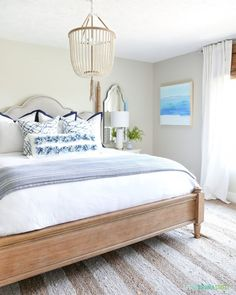 wooden home decor Coastal inspired guest bedroom with natural tones and a beachy feel. Natual colors and pops of blue home decor. Beautiful wooden beaded chandelier and coast art are the centerpieces. Coastal Bedrooms, Guest Bedrooms, Coastal Master Bedroom, Serene Bedroom, Blue Home Decor, Home Decor Bedroom, Bedroom Ideas, Bedroom Inspo, Bedroom Designs