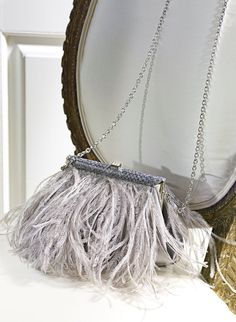 Confectionné en somptueux satin de soie, ce magnifique sac de soirée signé Ralph Lauren Collection est orné d'une bordure en python exotique et d'opulentes plumes d'autruche.