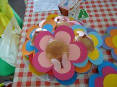 Bloemen - kartonnen bloemen met daarop een eierkoek en van snoeppapier en rood staafje snoep een vlinder