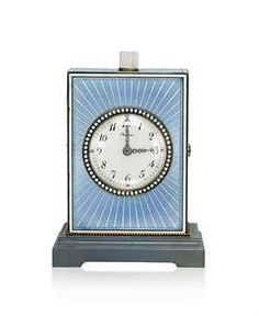 A BLUE ENAMEL MINUTE REPEATER DESK CLOCK, BY CARTIER  The circular white dial with Arabic numerals and rose-cut diamond hands within steely-blue guilloché enamelled rectangular-shaped case with beaded decoration to the light brown agate stepped base, moonstone plunge-repeat button, with key, 1910s.