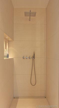 Dusche mit großformatigen Fliesen an Wand und Boden. Duschrinne an der Wand, beleuchtete Nische. #Fliesen #Duscherinne