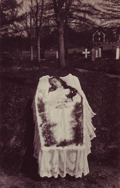 Deceased girl in her open coffin which looks like it is placed outside in a cemetery. I think it is a painted background.