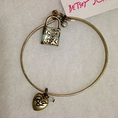 Betsey Johnson Bangle Gold, antique finished bangle with a heart charm engraved with BJ on the one side and  Betsey Johnson on the other side. It also has a padlock charm that says lovers and a zirconian dangling charm. Betsey Johnson Jewelry Bracelets
